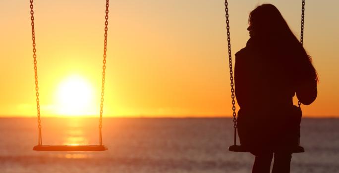 Kvinna sitter på en gunga och tittar på solnedgång