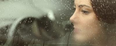 Kvinna med depression tittar ut genom en bildörr