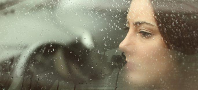 Ledsen kvinnan tittar ut genom en bildörr