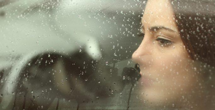 Deprimerad kvinnan tittar ut genom en bildörr