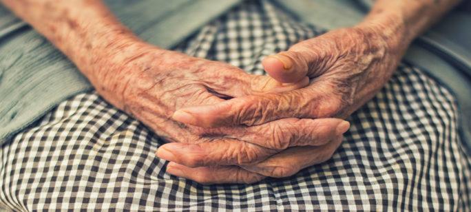 Äldre kvinnas händer knäppta över rutig kjol