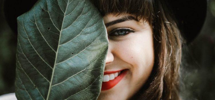 Leende kvinna som håller ett löv framför ansiktet