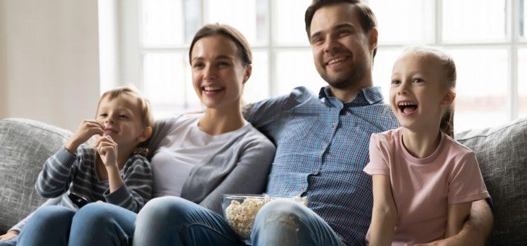 Familj tittar på tv och äter popcorn