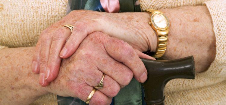 Äldre kvinna håller i en käpp