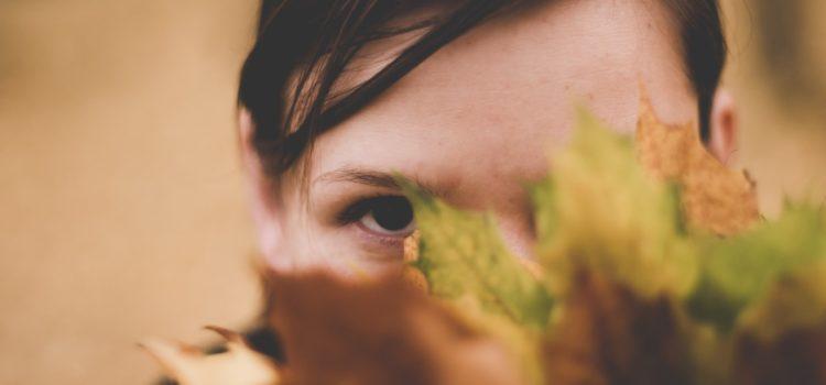 Kvinna med social ångest gömmer sig bakom löv