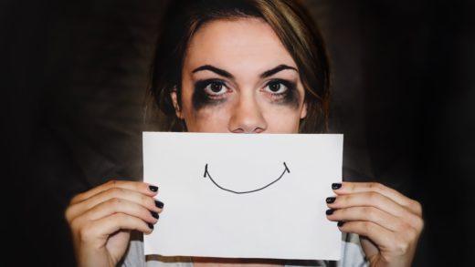 Deprimerad tjej håller upp ett papper med leende mun