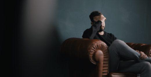 Man med ångest sitter på en soffa och tar sig för pannan