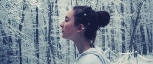 Tjej står i snötäckt skog.