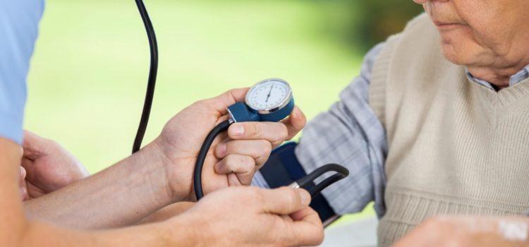 Läkare mäter blodtryck på äldre man